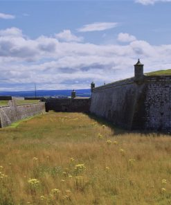We stand in a grass filled moat, surrounded by the massive walls and sentry towers of a British Army 1700's artillery fortification. In the far distance ahead of us is a gently rising ridge of land covered with forest and farmland. Above is a blue sky with some white clouds.