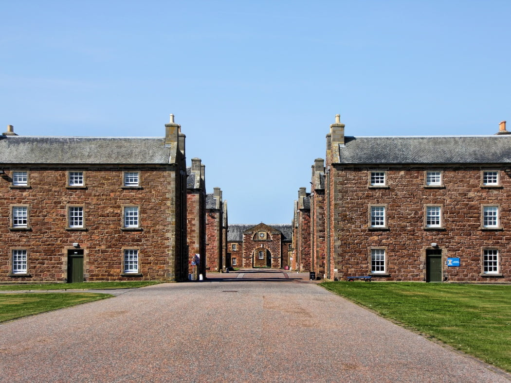 This is a view within the walls of the 1700's Fort George, which we visit on tour after Culloden and Clava. in front of us is a tarmac road running straight away between red stone barracks blocks, four on each side, gable on to the road and diminishing in the distance. Across the road in the distance is an archway in a building with a clock mounted above. The sky is pale blue.