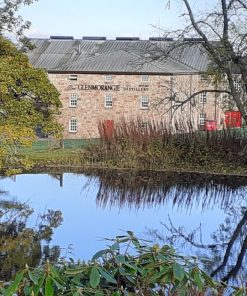 At one point on our Four Day North Coast 500 Tour from Inverness we stand at this pond, across which stands a building with ornate black lettering saying the Glenmorangie Distillery. The pond is reflecting trees and blue sky. On the far side the distillery building is 3 storeys, stone-built and with a corrugated metal roof.