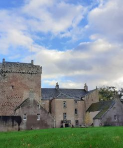 Kilravock Castle, near Inverness, is on our tour because it is the seat of Clan Rose. The foreground is grass. There are trees to left and right. A blue sky with clouds is above. The castle fills most of the picture. Left hand half of the castle is a tall square medieval grey stone keep. The right half is newer with portions from the 18th and 19th centuries.