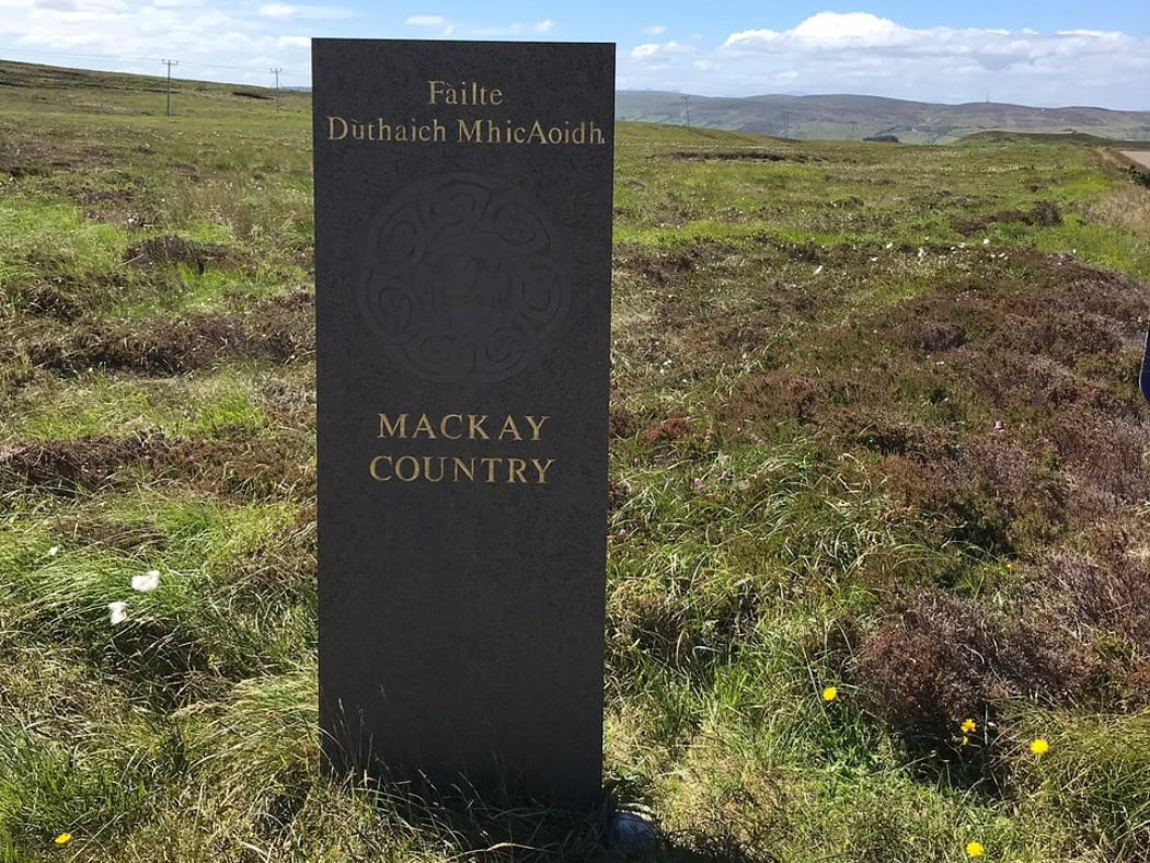 A modern rectangular standing stone about 6 feet high, with circular celtic design and inscribed with gold lettering says MACKAY COUNTRY is passed on our clan tour from Inverness. The stone stands in grass and heather, and a long hill ridge stands behind, with a cloudy blue sky above.