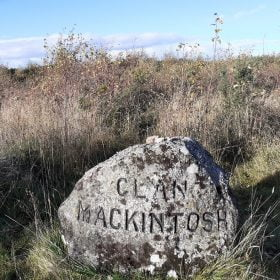 This is a close-up of a rough grave stone on Culloden Moor with the words Clan Mackintosh chiselled into it, visited on the Clan Mackintosh Tour from Inverness. The stone is in grass, with bushes behind, under a blue sky.