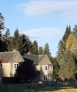 Moy Hall, near Inverness, visited on the Clan Mackintosh Tour is from the centre to the left. It is a 2-storey stone-built 20th century building with bow windows to the front and a grey slate roof. There are large mature trees behind, and a blue sky above.