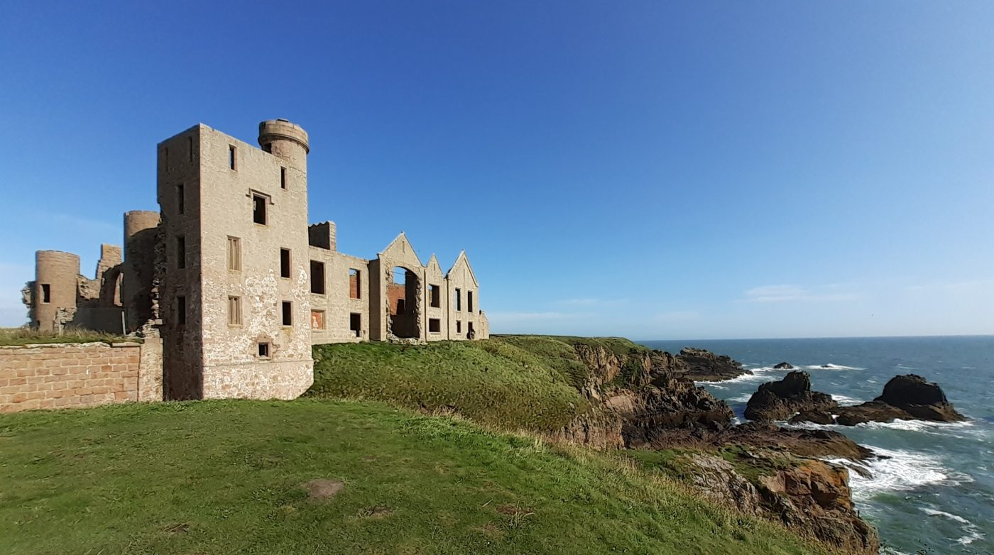 New Slains Castle is an extensive ruin on a clifftop setting on our North East 250 Tour. In this picture the sky and sea are blue, although there are white waves everywhere they crash against rocks.