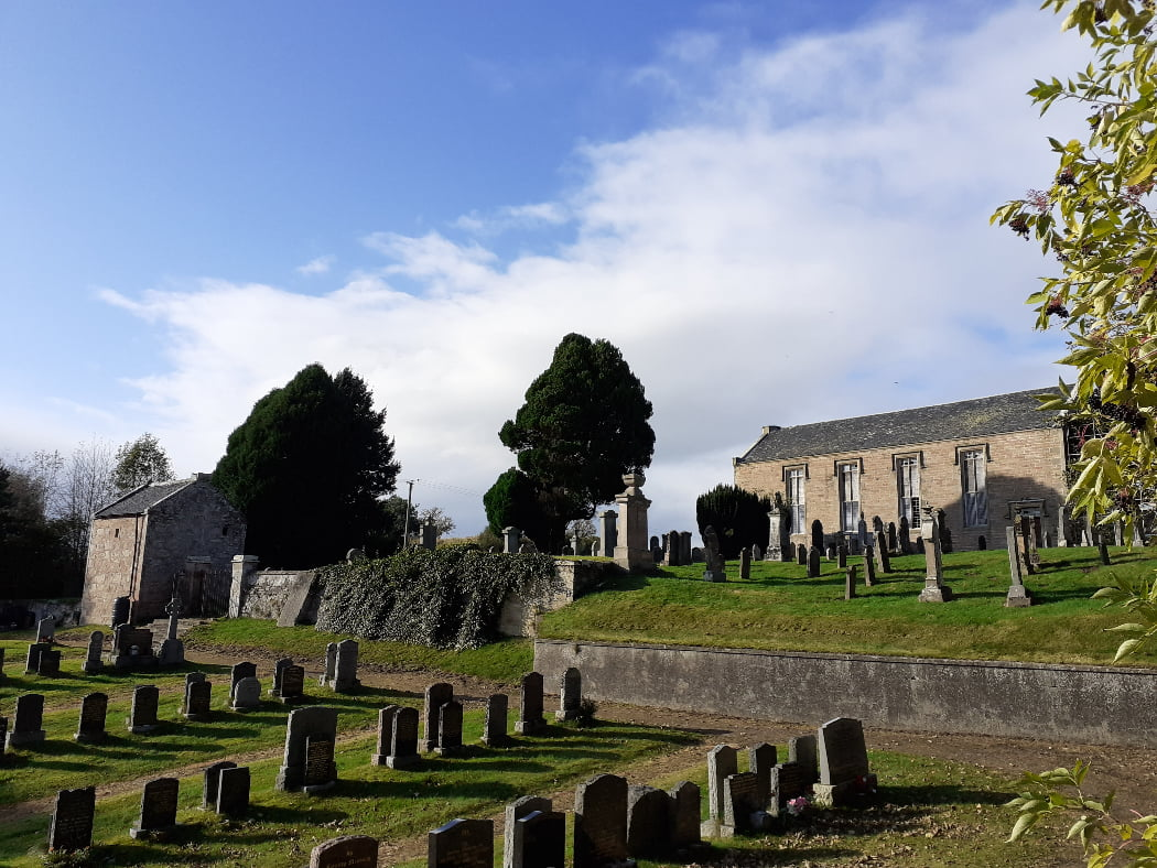 There are four rows of tombstones in the foreground, and then a retaining wall, and a sloping older churchyard above with more tombstones and a plain single storey church in back right. It has four tall windows in its long side, which is what is towards us. There are a couple of old yew trees and pines also visible, and an old grey building on the right hand side. The sky is blue but also a bit cloudy.