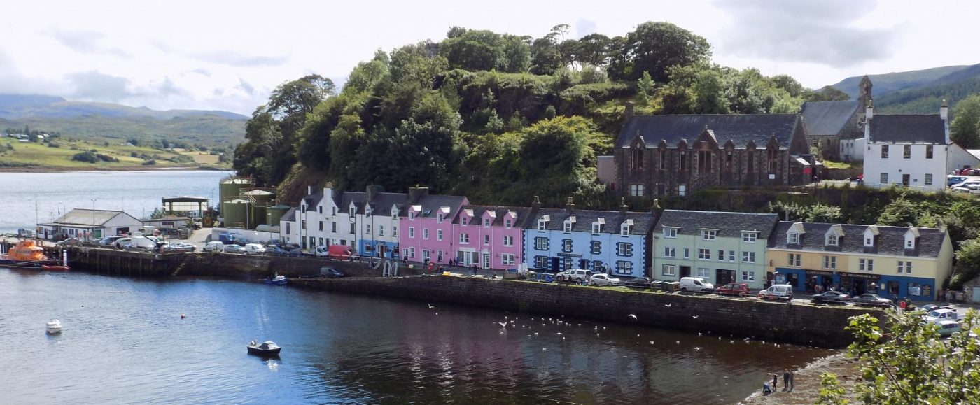 A line of brightly painted houses of different colours, along the harbour side in Portree on our Isle of Skye Tours from Inverness