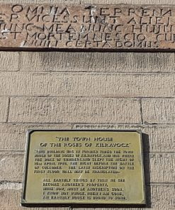 A sandstone block wall with an old stone plaque enscribed in latin. Below it is mounted a cast metal plaque idetifying the building as the town house of the Roses of Kilravock.