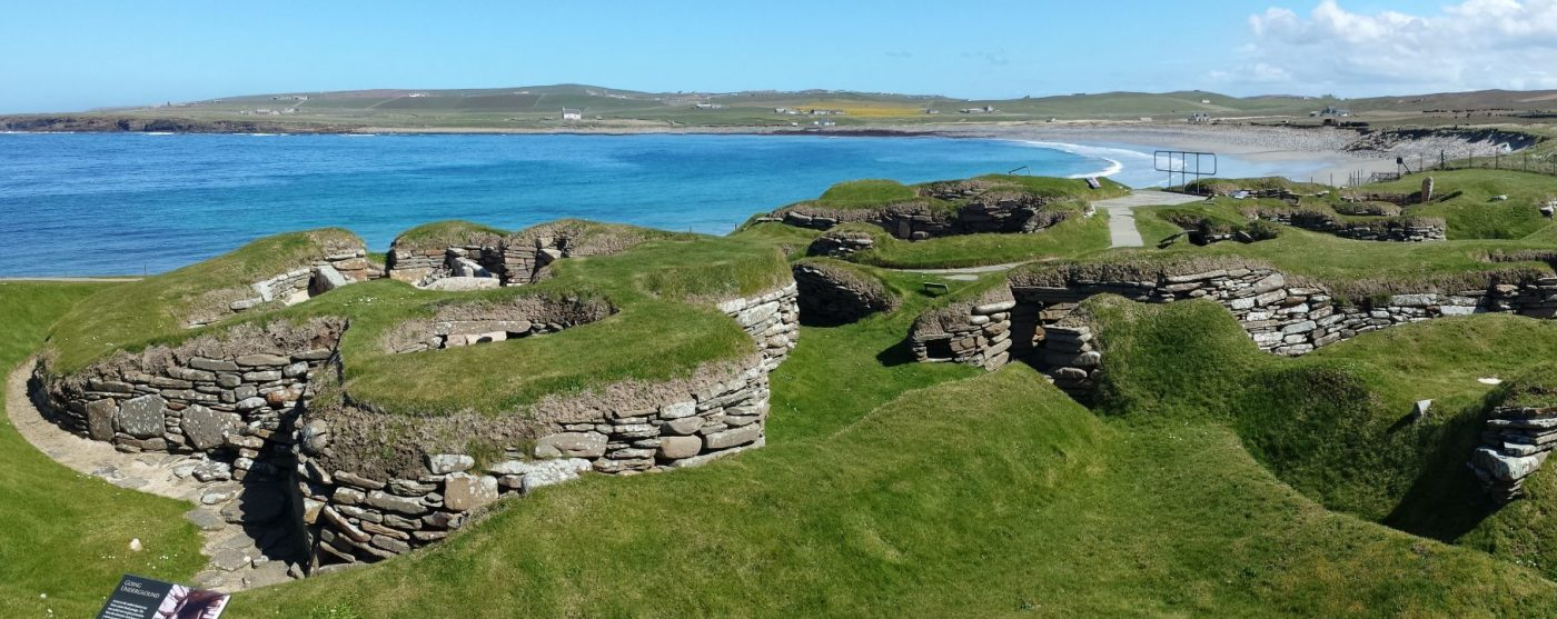 In the foreground are the low ruins of Skara Brae, Stone Age village, visited on our Orkney Tours from Inverness. Behind this is the broad crescent of the Bay Of Skaill, with a lazy Atlantic swell coming in over the sand, under a blue sky.