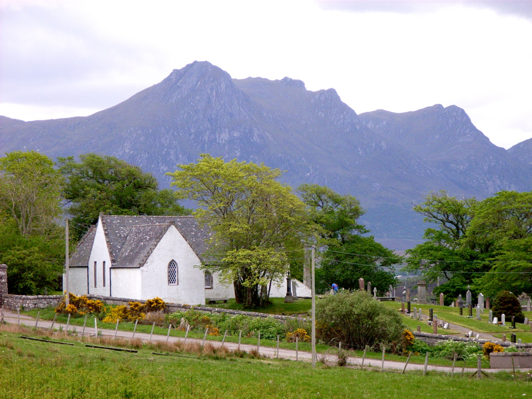 The foreground is a grassy field, then a single track road, crossing the field left to right. Far side of the road are shrubs and then the stone wall of the churchyard. Beyond the wall are tombstones and a very pretty white church with grey slate roof. Some large deciduous trees in the churchyard. A very large purple multi-peaked mountain in the background, under a white-cloud sky.