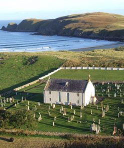 Arial shot of a two storey church, light grey with a dark grey slate roof. It stands in a square churchyard with many tombstones around it. There is a cove with a beach behind the church, and beyond it a bare grassy headland pushing out into the fairly calm blue ocean.