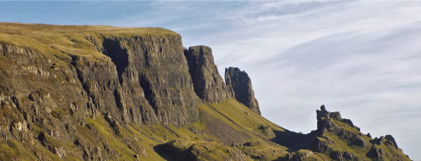 This wide picture is of a major landslip on the Trotternish Ridge. The sky above is blue and the grass is green, but overwhelmingly the great cliffs are black and shattered into cracks, chasms and pinnacles.The Quiraing on the Trotternish Peninsula on the Isle of Skye