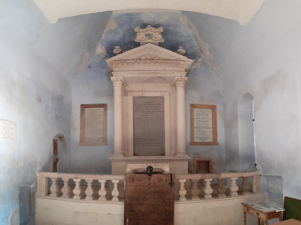 We are inside a light-blue painted mausoleum. Directly in front of us is a monument in white marble occupying the whole end wall. There is a platform surrounded by a balustrade, and centrally on the platform is an edifice comprising pillars to either side of a portico surmounted by an ornate pediment. There is a large tablet with writing on the wall at the rear of the portico, and a smaller tablet to each side.