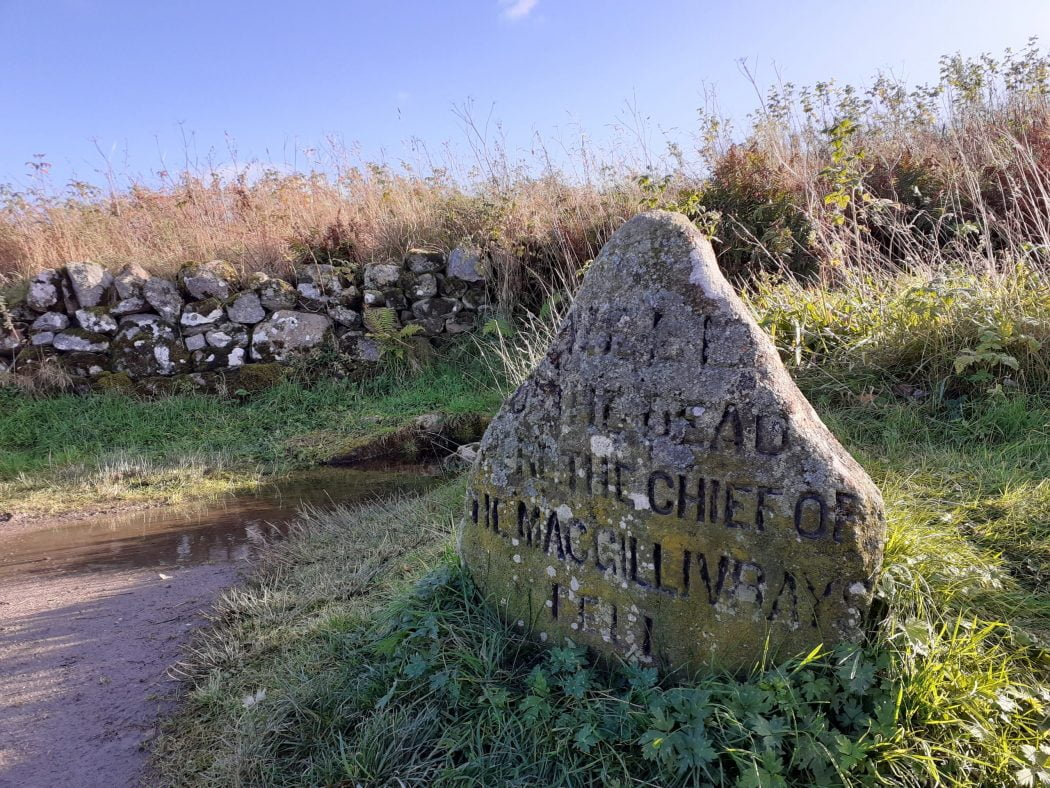 The foreground is a large stone (on the Culloden Battlefield and Clava Cairns Walking Tour) inscribed with the words Well of the Dead, Here the chief of the MacGillivrays Fell. A quarry dust path passes to the left, and the grass behind the stone terminated at the foot of a dry stone wall that crosses the picture right to left. Behind the wall are wild long grasses and shrubs, and above is a clear blue sky.