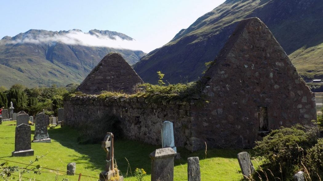 There is a churchyard with tombstones in the foreground, and a roofless ruined church filling most of the image. Behind, rising into a pale blue sky, are some very rugged mountains with just a little tonsure of clouds on them.