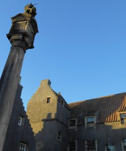 This is a close-up of the Culross (Cranesmuir) market pillar on our Outlander Tour from Glasgow. It is surmounted by a unicorn, and the sky above it is cloudless blue. Two buildings are visible, one to the left, behind the pillar, and the other, straight ahead, is Geilis Duncan's house from the filming. The buildings are painted dark grey in preparation for the filming.