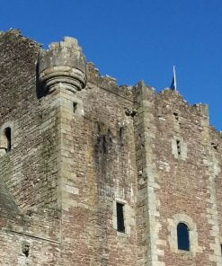 The grey keep of Doune Castle (Castle Leoch) rears into a cloudless blue sky, on the Outlander Tour from Glasgow. There is a flagpole centrally sited on the battlements of the keep, flying the Scottish flag.