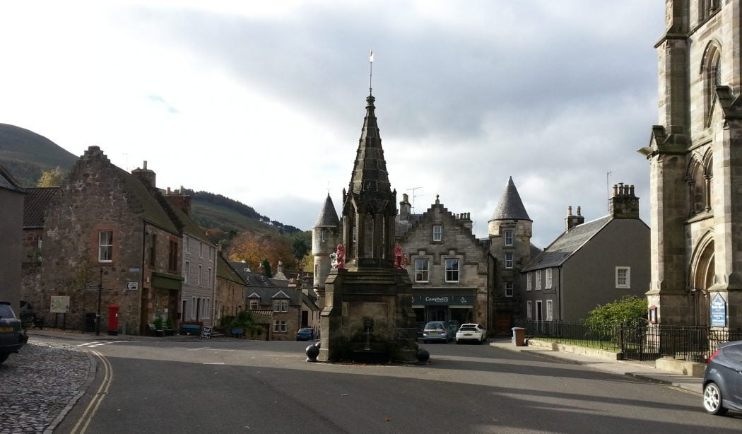 We stand in the middle of the street, in a historic old town. The architectural style says buildings of 1500's and 1600's, and right in the centre of the street is an ornate stone fountain. Just in-shot to the right is the edge of a church tower. Some cars are parked on the street. A steep hill rises in the leftmost background. The sky overhead is cloudy.