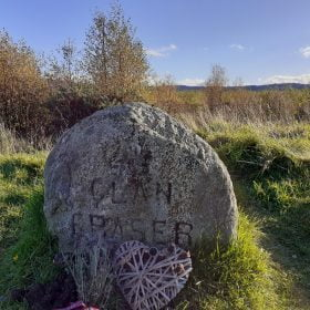 Foreground is the Fraser Clan Grave Stone on our Outlander Tour from Inverness. It is about 0.5m in height, grey with a rounded top, and the words Clan Fraser carved into the front. A woven heart ornament lies on the ground in front of the stone. There are shrubs and trees behind, and a bare hilltop ridge in the far distance. Above, the sky is blue.