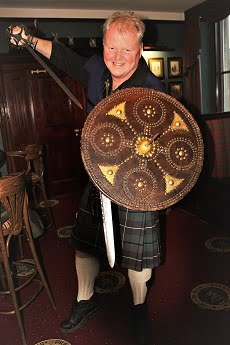 Hugh Allison is in the foreground in this image taken on the outlander tour from Inverness. He is inside a public room, and is kilted. He is holding a sword overarm in his right hand, and a shield and dirk (dagger) in his left hand. He is lunging towards the camera.
