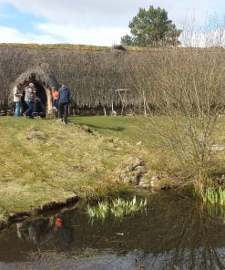 There is a small pond in the foreground. Up the grass slope behind it is a long thatched building with a single door towards the left hand end. There is a man and a woman dressed in farming 1700's costume at the left hand end of the building and five visitors in front of the door. The sky above is cloudy.