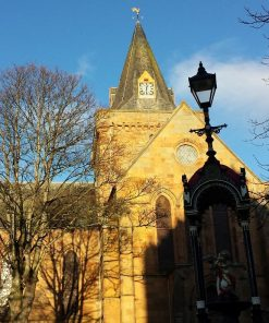 Dornoch Cathedral on our NC500 the North East day Tour is the main subject. Honey-coloured stone bathed in winter sunlight. A single spire, sporting a golden weathercock, rises into a blue sky. There us a clock on the spire. Trees bare of leaves occupy the foreground, together with an ornate black painted fountain, standing in shade.