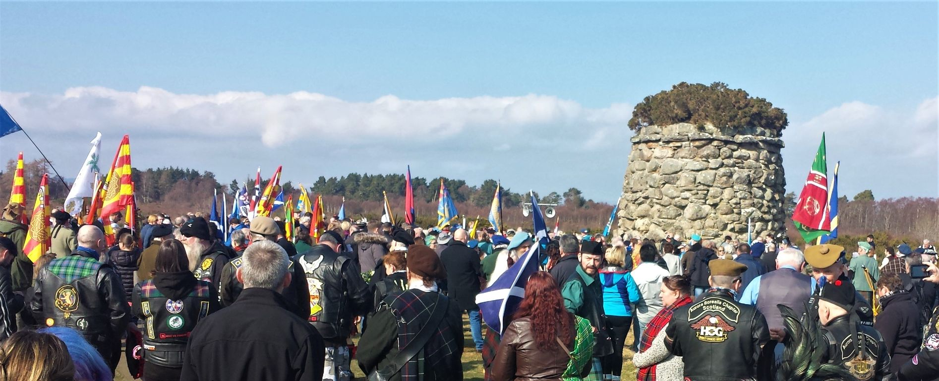 Scottish Clan Tours visit to the annual Anniversary Service at Culloden, by Inverness. A great crowd of people in the foreground with many colourful flags. The people are in every garb from motorcycle leathers to full traditional kilt. Mid-ground to the right is the main Culloden Memorial, standing 20 feet high with bushes on top. In the background is a forest, above which are light clouds and a blue sky.