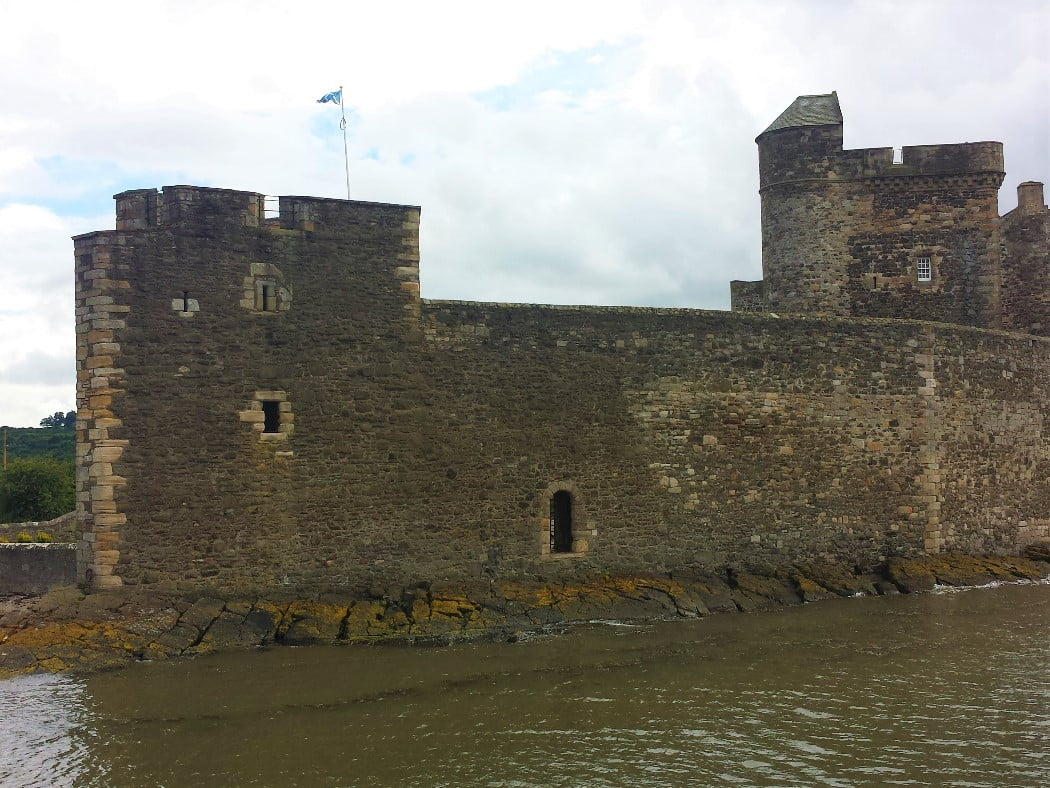 Nearly the whole image is 15th century Blackness Castle. It projects, on black and greenish rocks into a mud-coloured sea. The nearest low tower, at the left of the image and part of the curtain wall, has a flagpole flying a Scottish flag. The two higher towers rise from behind the curtain wall almost out of shot to the right. The sky above is cloudy.