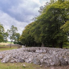 In front of us are two prehistoric cairns visited on our Multi Day Outlander Tours from Glasgow. They are surrounded by standing stones. They stand on grass, and are surrounded by mature deciduous trees in leaf. The sky above is cloudy.