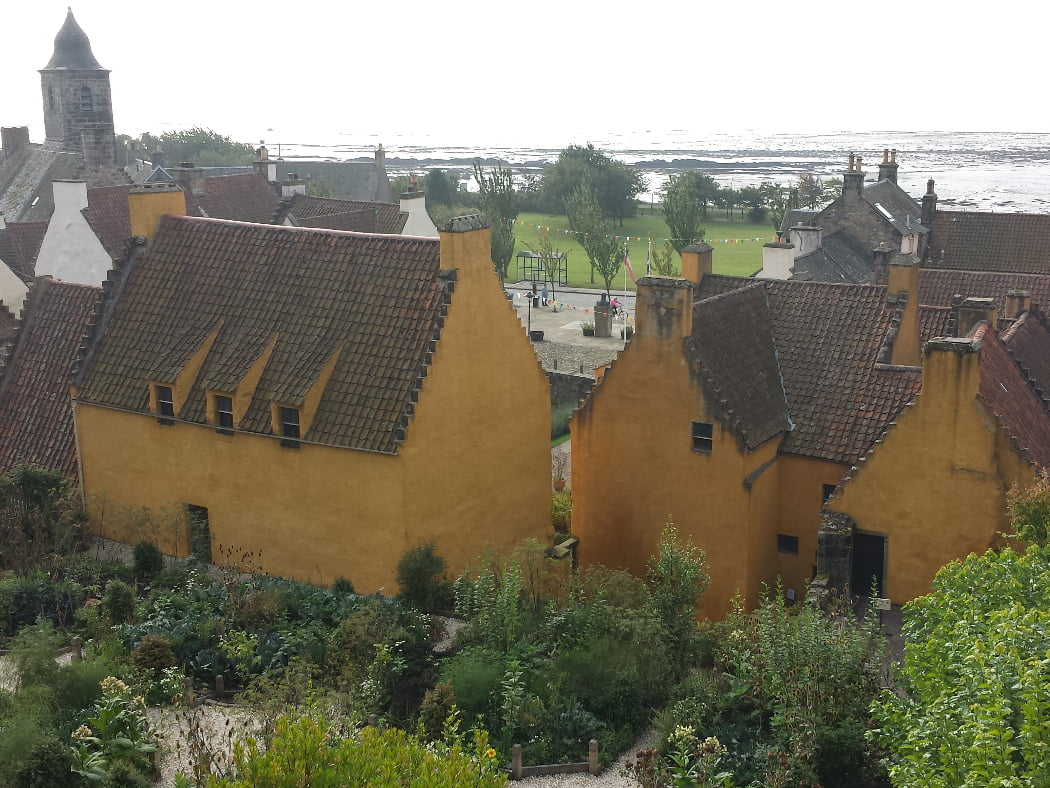 We are above a beautiful garden, which itself is behind a 1500's merchant palace, painted yellow and with pantiles on the roof. In front of the two buildings of the palace are some other old buildings, and to the left, a tolbooth tower. Beyond that, in the background, is the sea-shore.