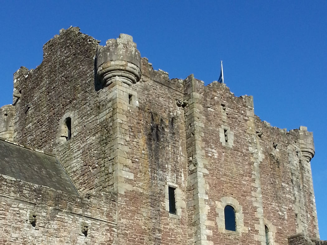 The grey keep of Doune Castle (Castle Leoch) rears into a cloudless blue sky, on the One Day Outlander Tour from Glasgow. There is a flagpole centrally sited on the battlements of the keep, flying the Scottish flag.