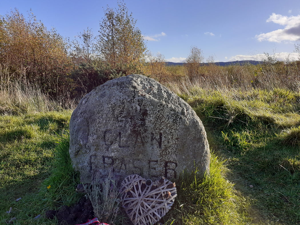 Foreground is the Fraser Clan Grave Stone on our One Day Outlander Tour from Inverness. It is about 0.5m in height, grey with a rounded top, and the words Clan Fraser carved into the front. A woven heart ornament lies on the ground in front of the stone. There are shrubs and trees behind, and a bare hilltop ridge in the far distance. Above, the sky is blue.