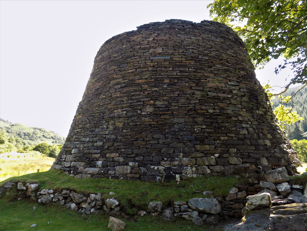 The 30-foot ruined tower filling this image is a broch. A large deciduous tree is to the right, and in the distance, to the left is a hillside covered in deciduous trees (all in leaf). It is a sunny day, though we are in the shade of the tower, and the sky is a cloudless very pale blue. and there is a blue sky above.