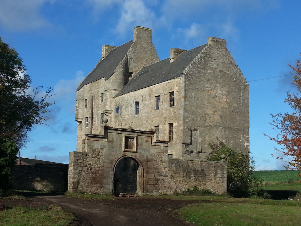 On our One Day Outlander Tour from Edinburgh is an ornate partial wall with archway, behind which the four-storey grey stone Towerhouse of Midhope Castle (Lallybroch) stands. The sky above is blue.