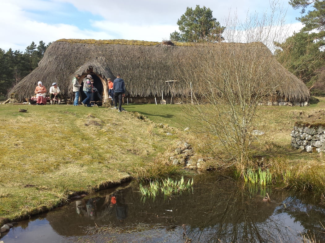 There is a small pond in the foreground of this shot taken on our Multi Day Outlander Tours from Edinburgh. Up the grass slope behind it is a long thatched building with a single door towards the left hand end. There is a man and a woman dressed in farming 1700's costume at the left hand end of the building and five visitors in front of the door. The sky above is cloudy.