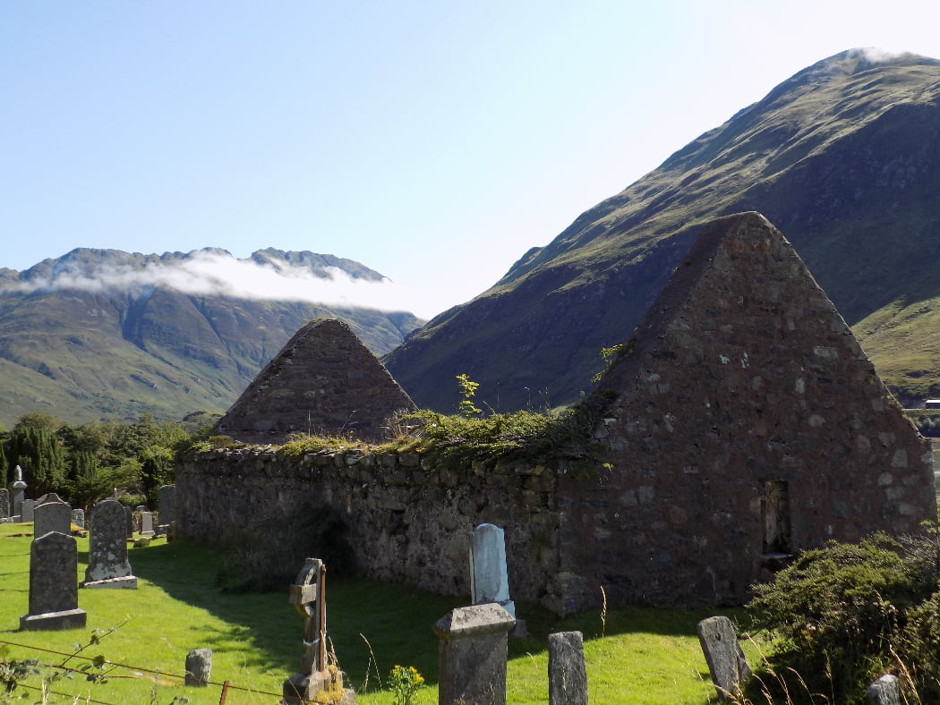 The churchyard with tombstones in the foreground is visited on our Multi Day Outlander Tours from Glasgow. This is a roofless ruined church filling most of the image. Behind, rising into a pale blue sky, are some very rugged mountains with just a little tonsure of clouds on them.