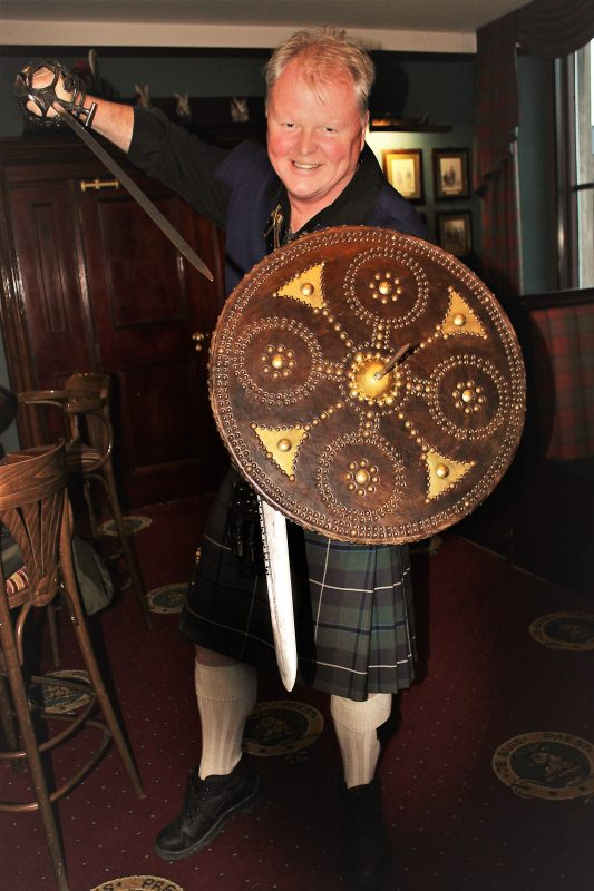 Hugh Allison is in the foreground in this image. He is inside a public room, and is kilted. He is holding a sword overarm in his right hand, and a shield and dirk (dagger) in his left hand. He is lunging towards the camera.