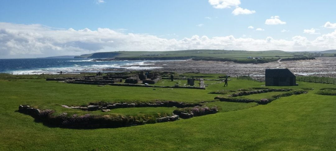 A sunny but windy/wild looking day on the tidal island called the Brough of Birsay. In the green grass of the foreground we can see the low foundations of Pictish and Viking settlement. In the middle distance we see the tidal crossing and in the background are the low rising green hills of Orkney Mainland.