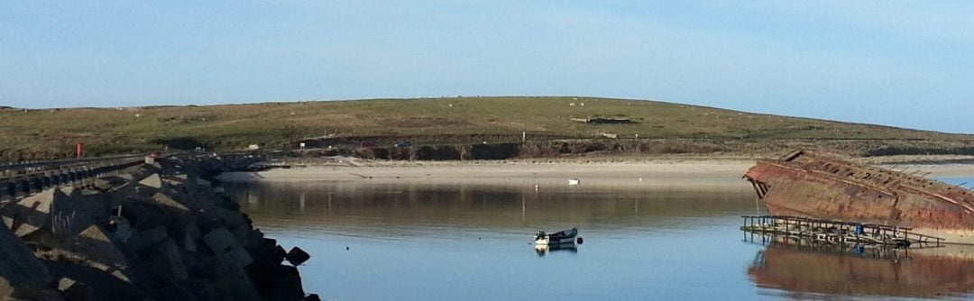 This is a wide picture of the Churchill Barriers we visit on our Orkney Tours from Inverness. On the left is the concrete block built WWII causeway called a Churchill Barrier. On the right is the rusting hulk of a war-time blockship. The ocean is still, and in the background a gentle green hill rises above a sandy beach.